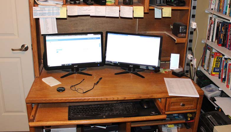 marks wooden office desk with two monitors